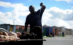 Cape Town-180906  Street vendor Phumlani Mayephu from khayelitsha cleaning the remening hair of smiley before cleaning them . His selling smiley full its R70 and half is R35. The Sheep head also know as Smiley is very popular in the township it used to be cooked only if threr was traditional cremony nowadays there are many places that clean and sell this delicacy,cooked or uncooked  Pictures Ayanda Ndamane/African/news/agency ANA