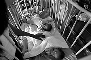 An orphaned child lying in a cot being comforted by a carer at ward 8 of the Government Hospital at Mbabane, Swaziland where children who are HIV+ are housed. The Kingdom of Swaziland (population 1.1m), a small, landlocked country in southern Africa was bordered by South Africa on three sides and Mozambique to the east, with Mbabane as its administrative capital. At the start of the 21st century, the country had the highest incidence per head of population of HIV/Aids in the world and and high levels of poverty mainly in rural areas where 75 per cent of the population lived.