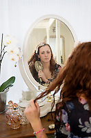 Young woman brushing her hair in front of mirror