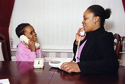 Social worker with young girl using the telephone,
