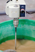 liquid being machine stirred with an industrial power mixer used for paints and other liquid solutions