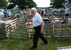 © Licensed to London News Pictures. <br /> 29/07/2014. <br /> <br /> Kirkbymoorside, United Kingdom<br /> <br /> A farmer walks next to the sheep pens before he unloads his sheep at the Ryedale agricultural show in North Yorkshire. The show was established in 1855 and is a traditional agricultural show renowned for its high standards of entries into the numerous livestock categories.<br /> <br /> Photo credit : Ian Forsyth/LNP