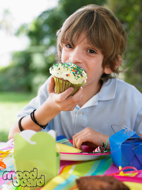 Portrait of young boy (10-12) eating cupcake at birthday party