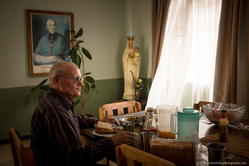 (2013)  Father Hermann goes for dinner at the mess hall of the church where he closby  lives in a small apartment.