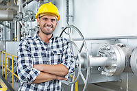 Young male worker standing arms crossed in industry
