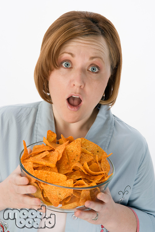 Mid-adult woman holding bowl of potato chips