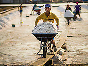09 MARCH 2015 - NA KHOK, SAMUT SAKHON, THAILAND: Burmese migrant workers on a salt farm near Samut Sakhon, Thailand, push wheelbarrows of salt to the warehouse during the salt harvest. The coastal provinces of Samut Sakhon and Samut Songkhram, about 60 miles from Bangkok, are the center of Thailand's sea salt industry. Salt farmers harvest salt from the waters of the Gulf of Siam by flooding fields and then letting them dry through evaporation, leaving a crust of salt behind. Salt is harvested through dry season, usually February to April. The 2014 salt harvest went well into May because the dry season lasted longer than normal. Last year's harvest resulted in a surplus of salt, driving prices down. Some warehouses are still storing salt from last year. It's been very dry so far this year and the 2015 harvest is running ahead of last year's bumper crop. One salt farmer said prices are down about 15 percent from last year.    PHOTO BY JACK KURTZ