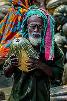 Melon Man: A man carries away a sole melon from the harbour adjacent to the fruit market, Dhaka Bangladesh.