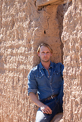 handsome blond man against a rustic building