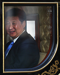 © Licensed to London News Pictures. 20/10/2015. London, UK. Chinese President Xi Jinping looks out from a carriage as he  travels to Buckingham Palace with Queen Elizabeth II during his four day State Visit to the United Kingdom. Photo credit: Peter Macdiarmid/LNP