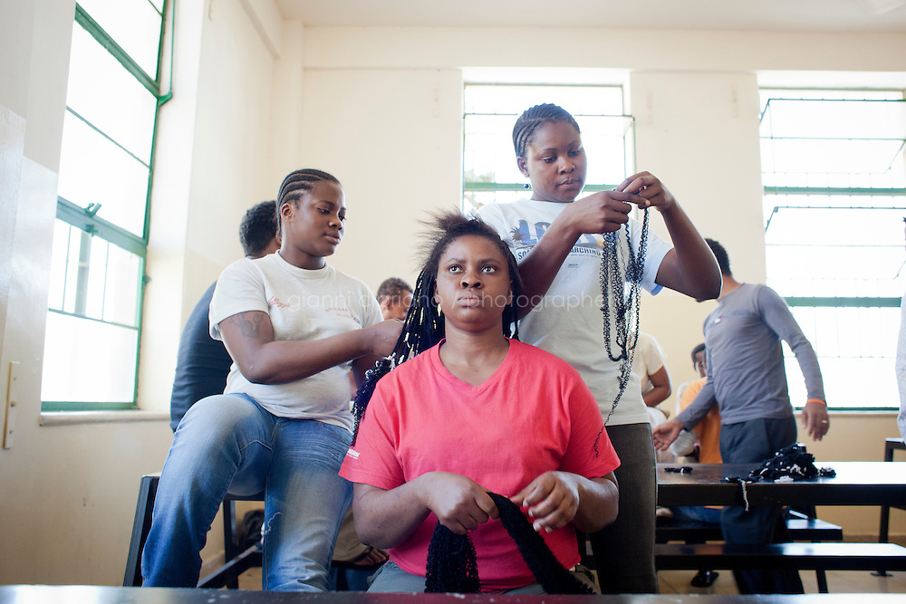 HAL FAR, MALTA - JUNE 20: Two sub-saharan immigants that arrived from Libya make braids for their friend (center) at the Lyster Barracks Closed Center, a detention center for immigrants in Hal Far (which translates as Rats' town), Malta, on June 20, 2011. All immigrants who enter in Malta illegally are detained. Upon arrival to Malta, irregular migrants and asylum seekers are sent to one of three dedicated immigration detention facilities: the Lyster Barracks Closed Centre, the Safi Closed Centre, and the Ta'kandja Closed Centre. Once apprehended by the authorities, immigrants remain in detention even after they apply for refugee status. detention lasts as long as it takes for asylum claims to be determined. This usually takes months; asylum seekers often wait five to 10 months for their first interview with the Refugee Commissioner. Asylum seekers may be detained for up to 12 months: at this point, if their claim is still pending, they are released and transferred to an Open Center.