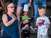 26 JUNE 2019 - CENTRAL CITY, IOWA: KAILEE LEWIS and her sons, KAYDEN LEWIS, 2, and PRESTON LEWIS, 4, cover their hearts during the National Anthem at the Linn County Fair. Summer is county fair season in Iowa. Most of Iowa's 99 counties host their county fairs before the Iowa State Fair, August 8-18 this year. The Linn County Fair runs June 26 - 30. The first county fair in Linn County was in 1855. The fair provides opportunities for 4-H members, FFA members and the youth of Linn County to showcase their accomplishments and talents and provide activities, entertainment and learning opportunities to the diverse citizens of Linn County and guests.       <br /> PHOTO BY JACK KURTZ