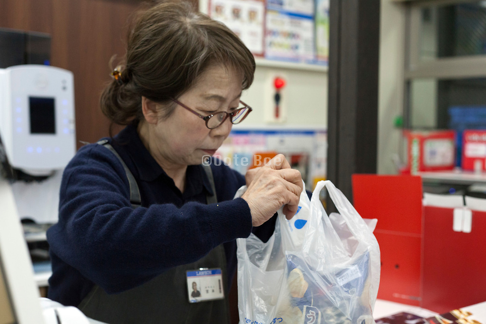 elderly woman working behind the counter at a convenient store Japan