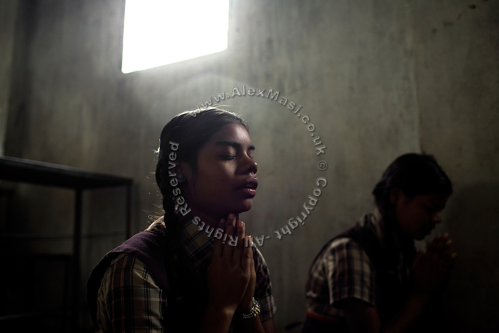 Jyoti, 14, (left) and her younger sister Poonam, 13, (right) are praying before starting lessons inside a classroom of the cozy, private school they regularly attend since 2011, located close to their newly built home in Oriya Basti, one of the water-contaminated colonies in Bhopal, central India, near the abandoned Union Carbide (now DOW Chemical) industrial complex, site of the infamous '1984 Gas Disaster'. The two girls are studying in Year 6, out of 12, in 2015-16.
