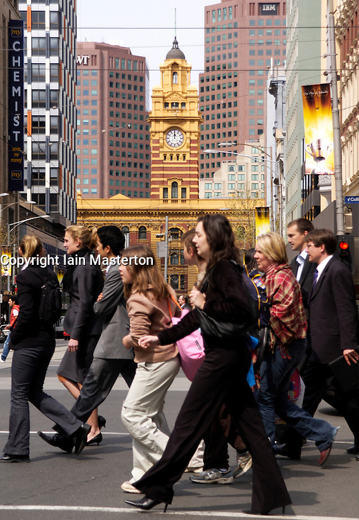 Pedestrians crossing busy Collins Street with famous Flinders Street Railway Station to rear in central Melbourne Australia