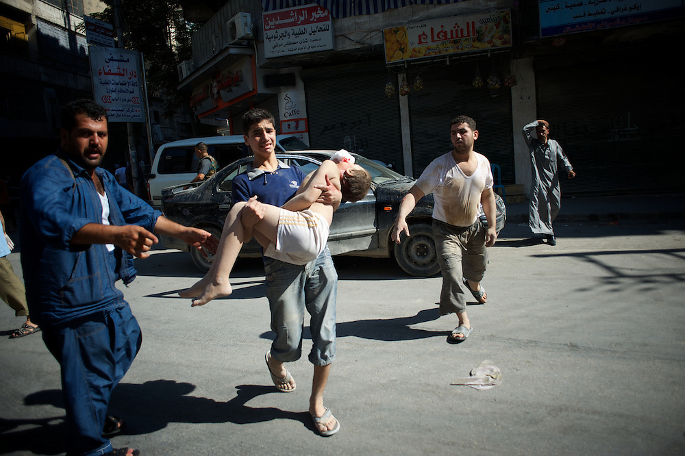 August 10, 2012 - Aleppo, Syria: A young man carries his brother, seriously injured minutes earlier by heavy shelling from the Syrian Army against a bakery in the residential area of Tariq Al-Bab in central Aleppo. At least 12 people have died and more the 20 got injured during the attack...The Syrian Army have in the past week increased their attacks on residential neighborhoods where Free Syria Army rebel fights have their positions in Syria's commercial capital, Aleppo. (Paulo Nunes dos Santos/Polaris)
