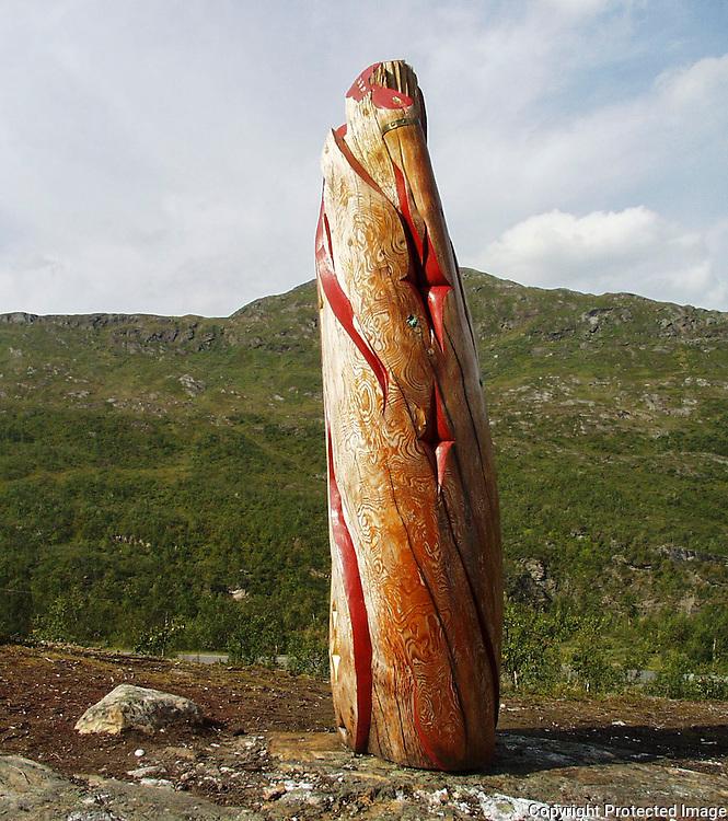 skulptur av Ingunn Utsi, P&aring;minnelsen, i sibirsk drivved. Krutfjellet bak<br /> dig