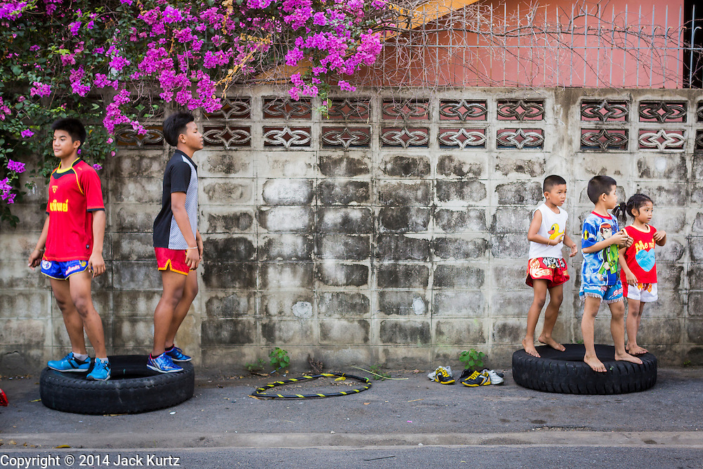 23 DECEMBER 2014 - BANGKOK, THAILAND:  Boxers loosen up by jumping up and down on old tires near the Kanisorn gym. The Kanisorn boxing gym is a small gym along the Wong Wian Yai - Samut Sakhon train tracks. Young people from the nearby communities come to the gym to learn Thai boxing. Muay Thai (Muai Thai) is a mixed martial art developed in Thailand. Muay Thai became widespread internationally in the twentieth century, when Thai boxers defeated other well known boxers. A professional league is governed by the World Muay Thai Council. Muay Thai is frequently seen as a way out of poverty for young Thais. Muay Thai professionals and champions are often celebrities in Thailand.    PHOTO BY JACK KURTZ