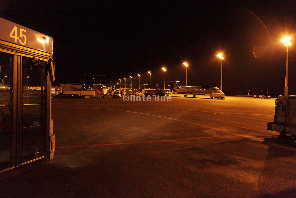 night airport tarmac with bus and airplane in the distance