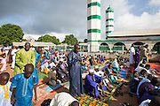 Gambian Muslims, both young and old, fill the local mosque in Sinchu and every available space outside to pray during the first day of Tabaski.<br /> Eid al-Adha, or known as Tabaski in West Africa, is also called the Feast of Sacrifice. Celebrated throughout the Muslim world is the second of the two Eid celebrations. During Tabaski every family will buy a goat which will be sacrificed and the meat distributed between the family and friends.