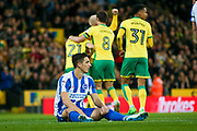 Brighton & Hove Albion central defender Lewis Dunk (5) sits down as Norwich City forward Alex Pritchard (21) scores a goal and celebrates to make the score 1-0 during the EFL Sky Bet Championship match between Norwich City and Brighton and Hove Albion at Carrow Road, Norwich, England on 21 April 2017. Photo by Simon Davies.
