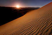 The setting sun casts dramatic shadows in the sand ripples on the dunes in Death Valley National Park, CA