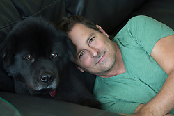handsome man leaning against a black Chow dog on a couch at home
