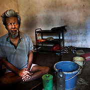 Wayan, 56 years old, blind and schizophrenic. His wife and son don't allow him inside the house. He is forced to live outside, in a small and dirty room without toilet and bathroom