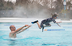 © Licensed to London News Pictures. 02/03/2018. London, UK. Doug O'Gorman plays with his daughter Lola as they brave the cold and snow at Hampton heated outdoor pool in south west London. The 'Beast from the East' and Storm Emma have brought extreme cold, ice and heavy snow to the UK. Photo credit: Peter Macdiarmid/LNP