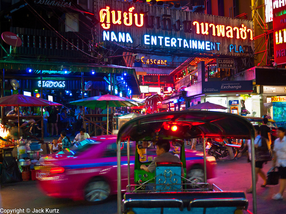 """13 JULY 2011 - BANGKOK, THAILAND:  Traffic in front of the entrance to the Nana Entertainment Plaza, a """"red light"""" district in Bangkok. Prostitution in Thailand is illegal, although in practice it is tolerated and partly regulated. Prostitution is practiced openly throughout the country. The number of prostitutes is difficult to determine, estimates vary widely. Since the Vietnam War, Thailand has gained international notoriety among travelers from many countries as a sex tourism destination. One estimate published in 2003 placed the trade at US$ 4.3 billion per year or about three percent of the Thai economy. It has been suggested that at least 10% of tourist dollars may be spent on the sex trade. According to a 2001 report by the World Health Organisation: """"There are between 150,000 and 200,000 sex workers (in Thailand).""""  PHOTO BY JACK KURTZ"""