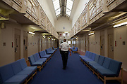 A female prison officer walks through the communal area inside one of the residential wings. HMP Styal, Wilmslow, Cheshire