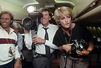 April 1984, USA --- In a playful moment aboard his campaign plane, presidential candidate Gary Hart uses a television camera belonging to the press. Hart is campaigning for the 1984 Democratic presidential nomination. --- Image by © Owen Franken