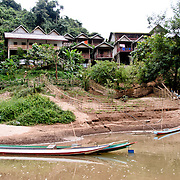 Boats and hotel rooms on the banks of the Nam Ou (River Ou) in Nong Khiaw in northern Laos. The small farm area will be covered with water when the river rises in the rainy season. At top right you can see a small section of the high bridge crossing the river.