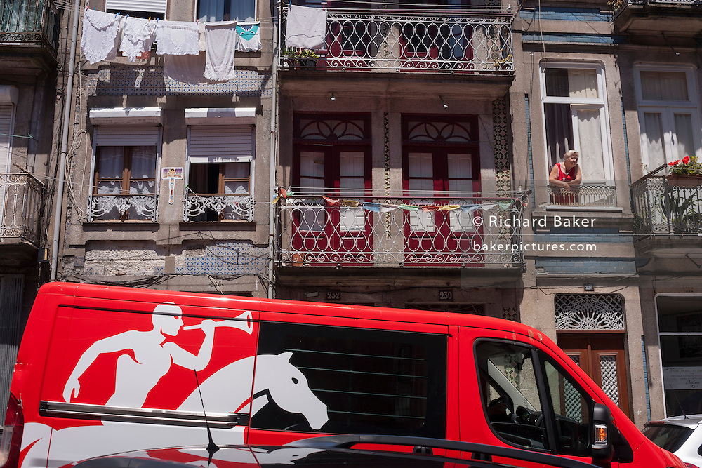 A parked van for Portuguese postal services CTT, below apartment balconies and a local resident, in Porto, Portugal.