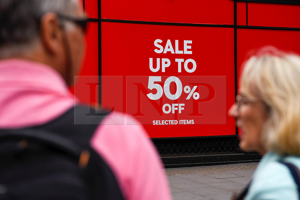 © Licensed to London News Pictures. 19/06/2019. LONDON, UK.  Tourists pass by a retail store on Regent Street as the Summer Sales season begins, with many stores offering large discounts to clear inventories.  As retailers continue to face the threat of online shopping, some well known high street store chains have proposed company voluntary arrangements (CVA) to try to reduce high fixed rental property costs.  Photo credit: Stephen Chung/LNP