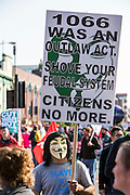 A man in an anonymous mask hiding a placard that reads '1066 was an outlaw act. Shove your feudal system. Citizens no more' at the TUC No to Austerity demo outside the Conservative party conference, Manchester. 4th October 2015
