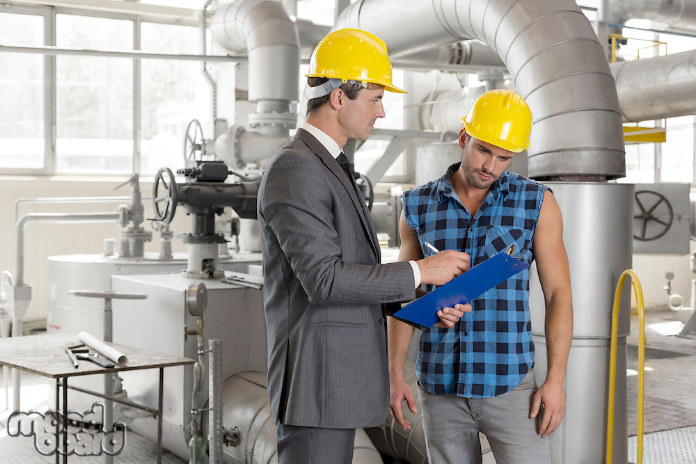 Male architect with worker discussing over clipboard in industry
