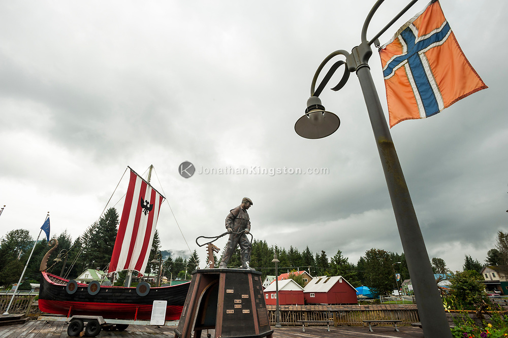 A Norwegian flag hangs on a light post above a statue of a fisherman and a replica of a viking ship in the town of Petersburg, Alaska.