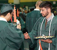 Senior Adrian Kemal Bayraktaroglu (right) holds his LED studded cap as he talks to senior Thang Tran backstage before Wright State University's 43rd Semiannual Commencement at the Nutter Center, Saturday, June 12, 2010.. Both are graduating Summa Cum Laude.