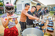 31 OCTOBER 2012 - YARANG, PATTANI, THAILAND: Soldiers in the Thai Army make merit by donating food to Wat Kohwai at a special Tak Bat before escorting villagers on a procession to Yala for Ok Phansa. Ok Phansa marks the end of the Buddhist 'Lent' and falls on the full moon of the eleventh lunar month (October). It's a day of joyful celebration and merit-making. For the members of Wat Kohwai, in Yarang District of Pattani, it was a even more special because it was the first time in eight years they've been able to celebrate Ok Phansa. The Buddhist community is surrounded by Muslim villages and it's been too dangerous to hold the boisterous celebration because of the Muslim insurgency that is very active in this area. This the year the Thai army sent a special group of soldiers to secure the village and accompany the villagers on their procession to Yala, a city  about 20 miles away.   PHOTO BY JACK KURTZ