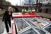 De Utrechtse wethouder Mirjam de Rijk (links) vaart mee met de Ecoboot. Het is de tweede elektrisch aangedreven boot die door de grachten van Utrecht gaat varen. De Ecoboot wordt ingezet voor het ophalen van vuilnis en kan kilo's legen en tegelijk glas, papier en restafval meenemen en extreem lange of zware vracht vervoeren. Het schip haalt dagelijks verschillende afvalstromen tegelijk op en is ook door derden in te huren.<br /> <br /> Alderman Mirjam de Rijk (left) is sailing with the 'Ecoboat' in Utrecht. It is the second electrical driven boat in the canals of Utrecht. The boat is going to be used to collect the garbage and can transport extreme long or heavy freight.
