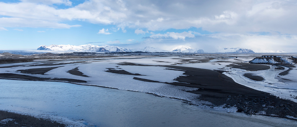 Volcanic lava with behind (far left) Skeioararjokull Glacier part of Vatnajokull Glacier in Vatnajokull National Park, South East Iceland