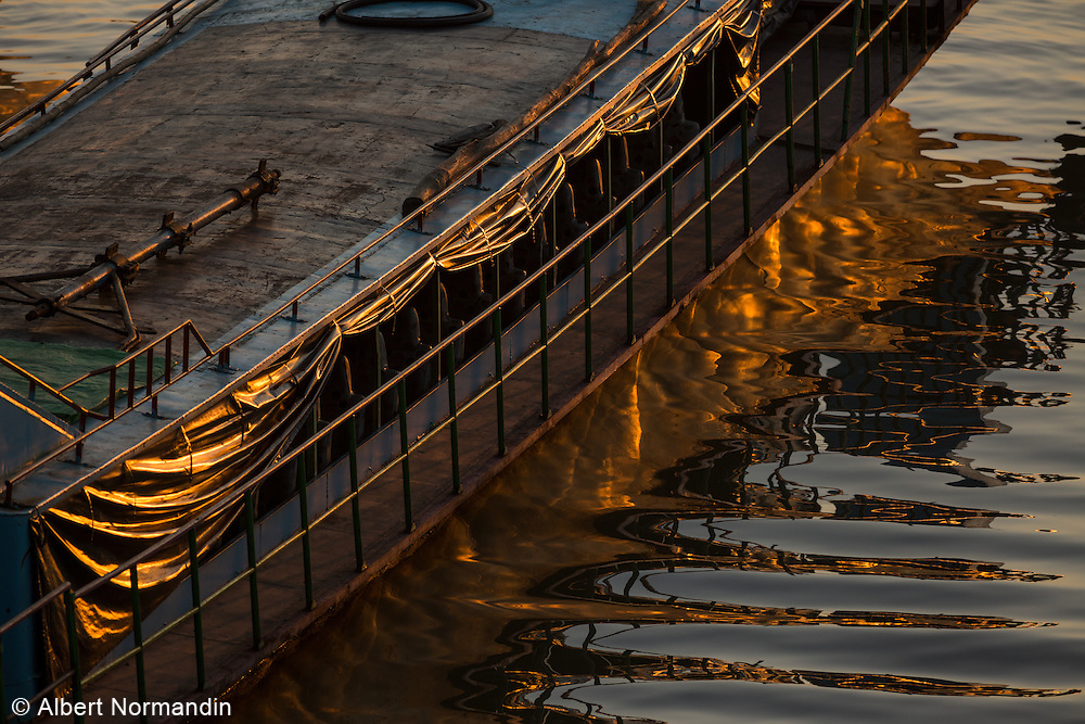 Golden ship reflection in Chindwin River at sunset
