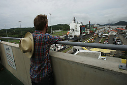 "A man stands atop the Miraflores Visitor Center Observation Deck and watches a ship pass through the Miraflores Lock in the Panama Canal.  Panama is poised to become the ""next Costa Rica"", though tourists have yet to begin flocking to the central american country.  The Capital, Panama City, is home to the Panama Canal and, due to the former US military presence, is one of the continents capitals most comfortable for people from the United States.  The country offers a variety of eco-tourism opportunities as well as a capital that mixes a modern feel with a colonial center."