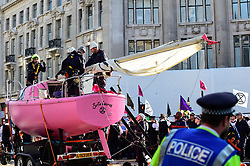 "© Licensed to London News Pictures. 19/04/2019. LONDON, UK.  Police officers tie down the mast of the pink boat ahead of its removal at Oxford Circus during ""London: International Rebellion"", on day five of a protest organised by Extinction Rebellion.  Protesters are demanding that governments take action against climate change.  Police have issued a section 14 order requiring protesters to convene at Marble Arch only so that the protest can continue.  Photo credit: Stephen Chung/LNP"
