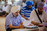 12 AUGUST 2012 - PHOENIX, AZ: Members of the Phoenix Sikh community pray and participate in Sunday services at the Guru Nank Dwara Ashram Sikh temple in central Phoenix. Guru Nank Dwara Ashram is the oldest of three Sikh temples in the Phoenix area. There are about 1,500 Sikh families in the area. Memorials have been held throughout the week to honor the Sikhs killed in the mass shooting in Wisconsin last week. Sunday's service included several mentions of the massacre and was attended by a number of people active in the Phoenix interfaith community.    PHOTO BY JACK KURTZ