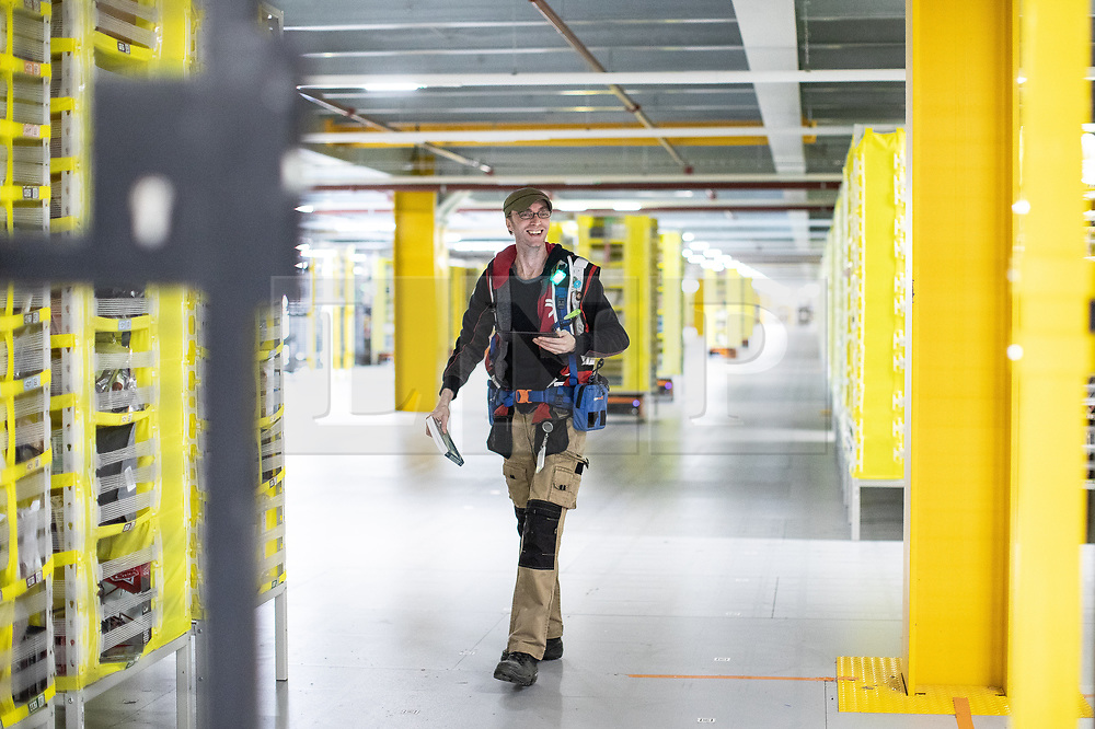 """© Licensed to London News Pictures . 04/12/2019. Manchester , UK . Staff member and Amazon Robotics expert ANDREW """"JIMMY"""" RIDDELL (42 from Oldham) halts robots inside a secure area to retrieve a book that has come astray . Inside the """"MAN1"""" Amazon fulfilment centre warehouse at Manchester Airport in the North West of England . Photo credit : Joel Goodman/LNP"""