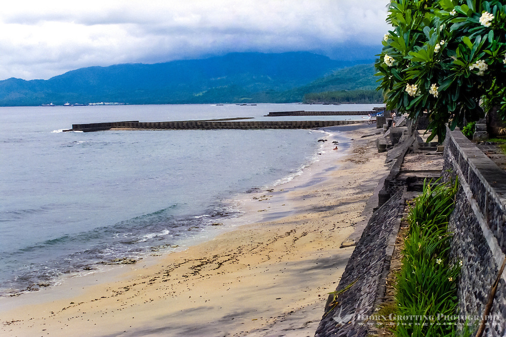 Bali, Karangasem, Candidasa. The beach is dominated by ugly concrete breakers. Looking west,the oil storage in Labuhan Amuk is visible in the background. Some are afraid that an oil spill here one day will destroy the beaches.