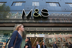 © licensed to London News Pictures. London, UK 22/05/2012. Shoppers going past a Marks & Spencer store in Oxford Street as M&S reported a 16 percent fall in full-year net profit today (22/05/12). Photo credit: Tolga Akmen/LNP