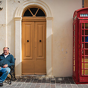 A man and a typical english red telephone box in San Lawrenz, a village of Gozo.